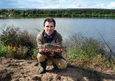 Fsherman con la carpa a specchi del pesce Fotografia Stock