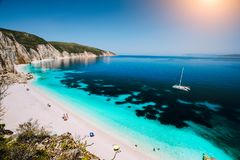 Fteri beach, Cephalonia Kefalonia, Greece. White catamaran yacht in clear blue sea water. Tourists on sandy beach near royalty free stock image