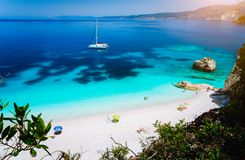 Fteri beach, Cephalonia Kefalonia, Greece. White catamaran yacht in clear blue sea water. Tourists on sandy beach near royalty free stock photos
