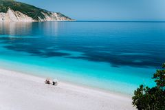 Fteri beach, Kefalonia, Greece. Lonely unrecognizable tourist couple hiding from sun umbrella chill relax near clear royalty free stock images