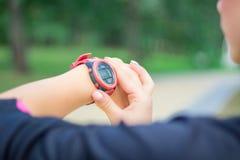 Ftitness girl checks stopwatch tracker on her wrist during runni Stock Image