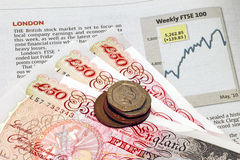 FTSE financial chart. An image of a wad of British currency & coins against the London stock exchange chart royalty free stock photography
