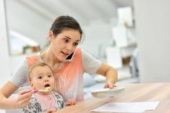 Fütterungsbaby der beschäftigten Mutter und Unterhaltung am Telefon Stockfotografie