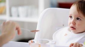 Fütterungsbaby der Mutter mit Püree zu Hause stock video
