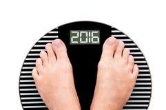 2016 Fuß auf einer Gewichtsskala lokalisiert auf Weiß Lizenzfreies Stockbild