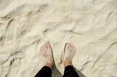 Fuß auf Sand am Strand Stockbild