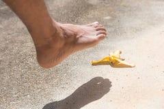 Fuß, bevor Bananenschale auf Boden geglitten wird Stockfoto