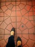 Fuß, der auf abstrakte Zementstraße geht Lizenzfreie Stockfotos