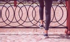 Fuß der jungen Mädchen in den Jeans und in den Turnschuhen trägt die Schuhe zur Schau, die auf Straße gehen Stockfotografie