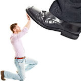 Fuß des Geschäftsmannes, der auf kleinen Geschäftsmann tritt Lizenzfreies Stockbild