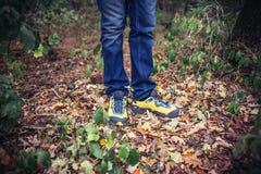 Fuß-Mann, der auf Fall in den Park auf Herbstlaub geht lebensstil Stockfotos