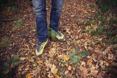 Fuß-Mann, der auf Fall in den Park auf Herbstlaub geht lebensstil Stockbilder