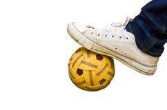 Fuß und alte Schuhe auf Rattanball lizenzfreie stockfotos