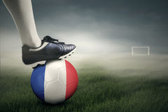 Fuß und ein Fußball am Feld Lizenzfreie Stockbilder