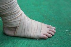 Fuß und Knöchel verletzt mit Verband auf grünem Hintergrund Lizenzfreies Stockfoto