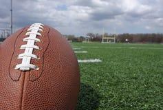 Fußball auf dem Feld mit Torpfostenhintergrund Lizenzfreie Stockfotografie