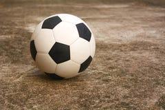 Fußball auf dem Zementboden Lizenzfreie Stockbilder