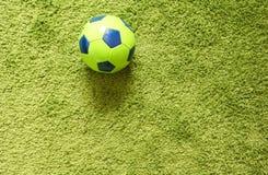 Fußball-Fußball auf einem künstlichen Gras der grünen Oberflächennachahmung Trägt Fotografie zur Schau Lizenzfreies Stockbild