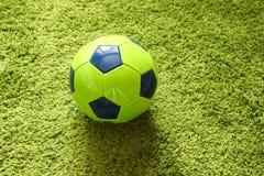 Fußball-Fußball auf einem künstlichen Gras der grünen Oberflächennachahmung Trägt Fotografie zur Schau Lizenzfreie Stockfotografie