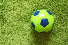 Fußball-Fußball auf einem künstlichen Gras der grünen Oberflächennachahmung Trägt Fotografie zur Schau Stockfotos