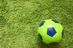 Fußball-Fußball auf einem künstlichen Gras der grünen Oberflächennachahmung Trägt Fotografie zur Schau Lizenzfreies Stockfoto