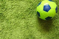 Fußball-Fußball auf einem künstlichen Gras der grünen Oberflächennachahmung Trägt Fotografie zur Schau Lizenzfreie Stockbilder
