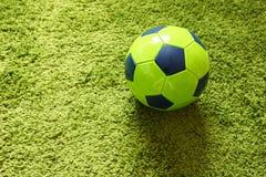 Fußball-Fußball auf einem künstlichen Gras der grünen Oberflächennachahmung Trägt Fotografie zur Schau Stockfotografie