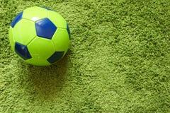 Fußball-Fußball auf einem künstlichen Gras der grünen Oberflächennachahmung Trägt Fotografie zur Schau Lizenzfreie Stockfotos