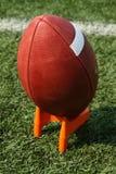 Fußball auf einem tretenden T-Stück Stockfotografie