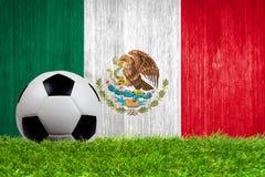Fußball auf Gras mit Mexiko-Flaggenhintergrund Lizenzfreie Stockfotos