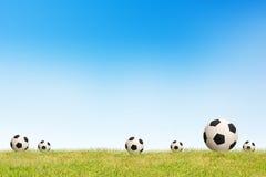 Fußball auf Grashimmelhintergrund Stockfotos