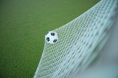 Fußball der Wiedergabe 3d im Ziel Fußball im Netz mit hellem Hintergrund des Scheinwerfers und des Stadions, Erfolgskonzept Lizenzfreie Stockbilder