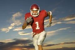 Fußball, der zurück mit Kugel läuft Stockfoto