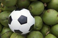Fußball-Fußball, der bei den frischen grünen Kokosnüssen liegt Stockbild