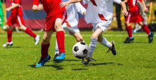 Fußball-Fußball-Tritt Fußballspielerduell Kinder, die Fußballspiel auf Sport-Feld spielen Jungen-Spiel-Fußballspiel auf grünem Gr Lizenzfreies Stockfoto