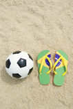 Fußball-Fußball und Flipflops auf brasilianischem Strand Stockfotos