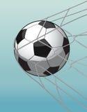 Fußball im Zielnetz auf dem blauen Hintergrund. Lizenzfreies Stockbild