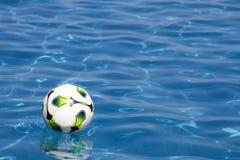 Fußball-Kugel im Swimmingpool Stockfoto