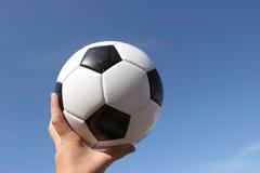 Fußball-Kugel mit der Hand Lizenzfreies Stockbild