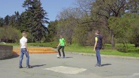 Fußball mit drei Jungenspielen im Park, viertes Jungenreiten auf Trittroller stock footage