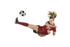 Fußball-Spieler, der Kugel im mittleren Sprung tritt Lizenzfreie Stockfotos