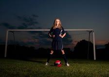 Fußball-Spieler mit Ball und Ziel bei Sonnenuntergang Lizenzfreie Stockfotos