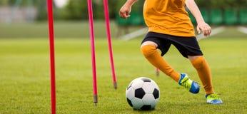 Fußball-Spieler mit Fußball-laufendem Slalom um Trainings-Stöcke Fußball-Geschwindigkeits-Training lizenzfreies stockfoto