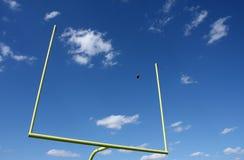 Fußball trat durch die Torpfosten stockfotografie