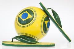 Fußball und Flipflops mit Brasilien-Flagge Lizenzfreies Stockfoto