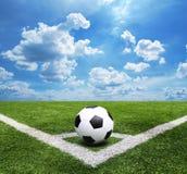 Fußball und Fußballplatz bedecken Hintergrund des blauen Himmels des Stadions mit Gras Lizenzfreie Stockfotos