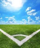 Fußball und Fußballplatz bedecken Hintergrund des blauen Himmels des Stadions mit Gras Stockfotografie