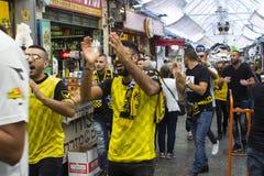 Fußballanhänger im Beitar Jerusalem-Streifen marschieren hinunter das Mall der Markthalle Mahane Yehuda in Jerusalem Israel Stockbilder