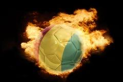 Fußballball mit der Flagge der Guine auf Feuer stockfotos