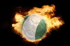 Fußballball mit der Flagge von Nigeria auf Feuer Lizenzfreie Stockbilder